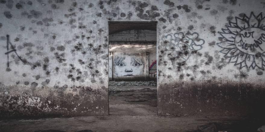 Betonmur med skimmelsvamp og ansigt